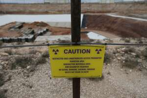A caution sign surrounding the low-level radioactive waste site at Waste Control Specialists (WCS) near Andrews, Texas. WCS provides services to store low-level nuclear waste and is in the process of applying for a license to be an interim storage facility for high-level radioactive waste. Opposition has mostly stemmed from activists outside the area but some residents are also voicing concerns about their city becoming the nation's dump site for potentially hazardous nuclear material. The Governmental Nuclear Regulatory Commission (NRC) has held hearings regarding the potential environmental impact of permitting WCS in far West Texas and activists along with proponents have been vocal in those hearings. (Kin Man Hui/San Antonio Express-News)