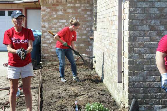 Volunteers for Keller Williams' RED Day work in a yard in Humble on Monday, May 10, to help a family in the community that was affected by Hurricane Harvey.