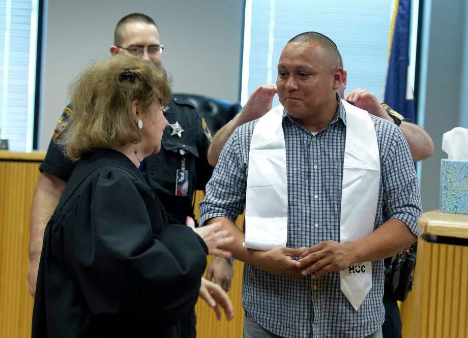 Javier Cervantes speaks to 359th state District Court Judge Kathleen Hamilton after presenting her with his Houston Community College graduation stole during the third anniversary of the Veterans Treatment Court at the Alan B. Sadler Commissioners Court Building, Wednesday, May 9, 2018, in Conroe. Cervantes, a graduate of the Veterans Treatment Court, spoke about his life after successfully completing the treatment program. The specialty court focuses on giving veterans with felony or misdemeanor charges a chance to join an outpatient treatment program. Photo: Jason Fochtman, Staff Photographer / © 2018 Houston Chronicle