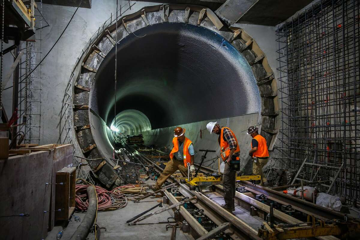 Workers David Lopez (left) and William Butler (center) do construction on the central subway at the Moscone station in San Francisco, Calif., on Wednesday, Sept. 13, 2017.