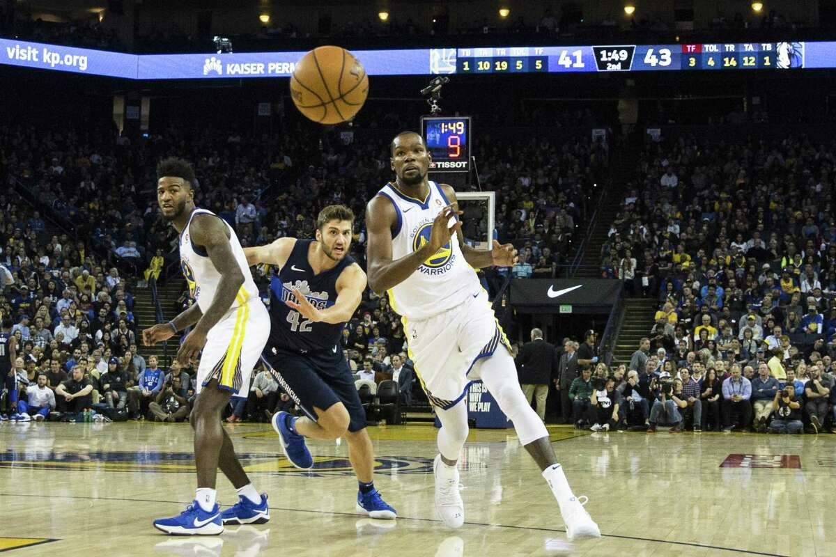 Kevin Durant #35 of the Golden State Warriors catches a pass from teammate Klay Thompson #11as he runs pasts a screen during the second quarter of their NBA basketball game against the Dallas Mavericks at Oracle Arena in Oakland, Calif. on Thursday, Dec. 14, 2017.