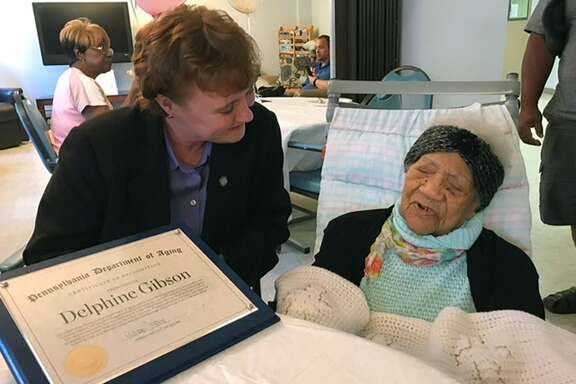 In this photo provided by Pennsylvania's Department of Aging, Delphine Gibson, right, is visited by Aging Secretary Teresa Osborne, at AristaCare Thursday, Aug. 17, 2017, in Huntingdon Park, Pa. Gibson, the oldest known living person in the United States celebrated her 114th birthday on Thursday in Pennsylvania. (Drew Wilburne/Pennsylvania Department of Aging via AP)