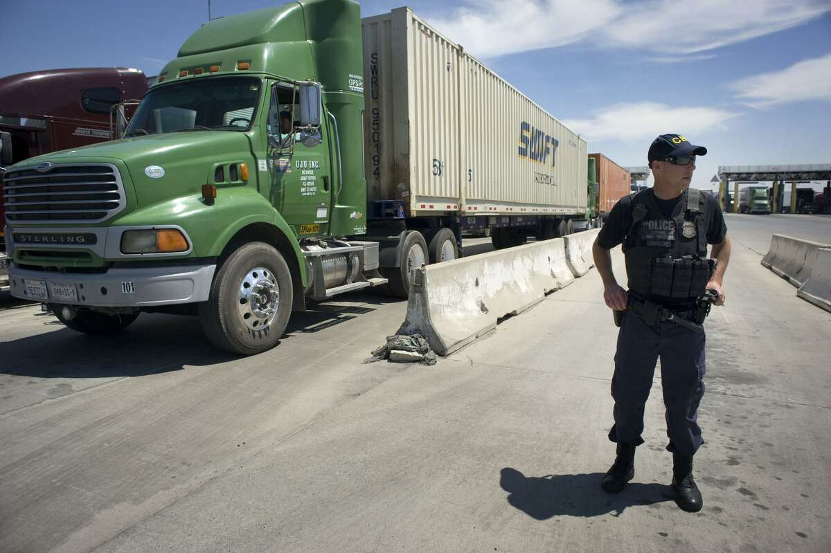 A U.S. Customs and Border Protection (CBP) officer stands next to a line of trucks that will undergo secondary inspection at the Otay Mesa Cargo Port of Entry in San Diego on May 23, 2017. MUST CREDIT: Bloomberg photo by David Maung.