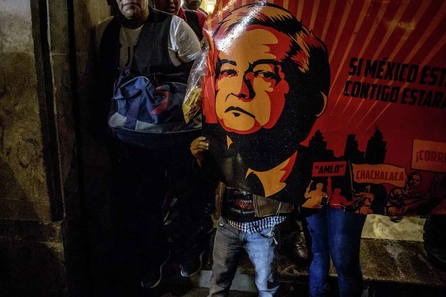 Supporters hold a sign displaying an image of Andres Manuel Lopez Obrador, presidential candidate of the National Regeneration Movement Party (MORENA), during the first presidential debate outside the Palace of Mining in Mexico City, Mexico, on Sunday, April 22, 2018. Mexico's peso, the world's best-performing currency this year, will probably depreciate as attention turns from Nafta optimism to political risks associated with presidential front-runner Lopez Obrador. Photographer: Alejandro Cegarra/Bloomberg Photo: Alejandro Cegarra / Bloomberg / © 2018 Bloomberg Finance LP