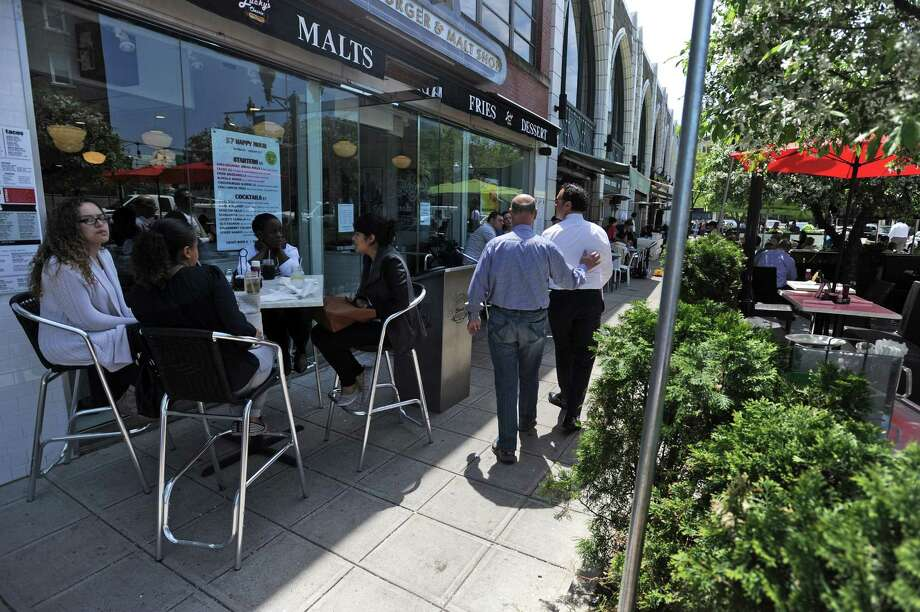 Pedestrians Walk Past Outdoor Seating For The Restaurants On Bedford St During A Warm Day