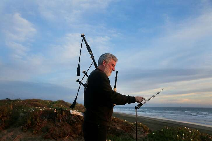 Jim Motch sets up a music stand for his tablet containing pdfs of music before playing from the cliff above Ocean Beach on Friday, May 4, 2018 in San Francisco, Calif.  Motch began learning to play the bagpipe when his mother became ill as a way to give back to her.