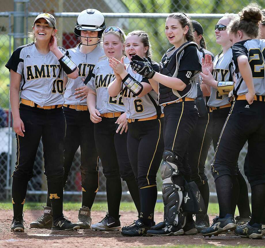 The Spartans celebrate Brooke Matyasovsky's over-the-fence homerun against Sacred Heart Thursday, May 10, 2018, at Sacred Heart Academy in Hamden. Amity won, 15-3. Photo: Catherine Avalone, Hearst Connecticut Media / New Haven Register