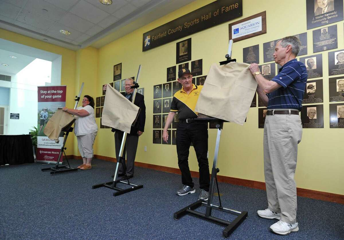 From right, Laddie Lawrence, Jim Dolan, Ralph King and Linda LaJoie Lay unveil the new plaques for the 2017 inductees into the Fairfield County Hall of Fame during a ceremony inside UConn Stamford in downtown Stamford, Conn. on Thursday, May 10, 2018. LaJoie Lay was representing her brother Randy LaJoie and Ralph King was represented former soccer player Phil Kydes, whom he coached in high school.