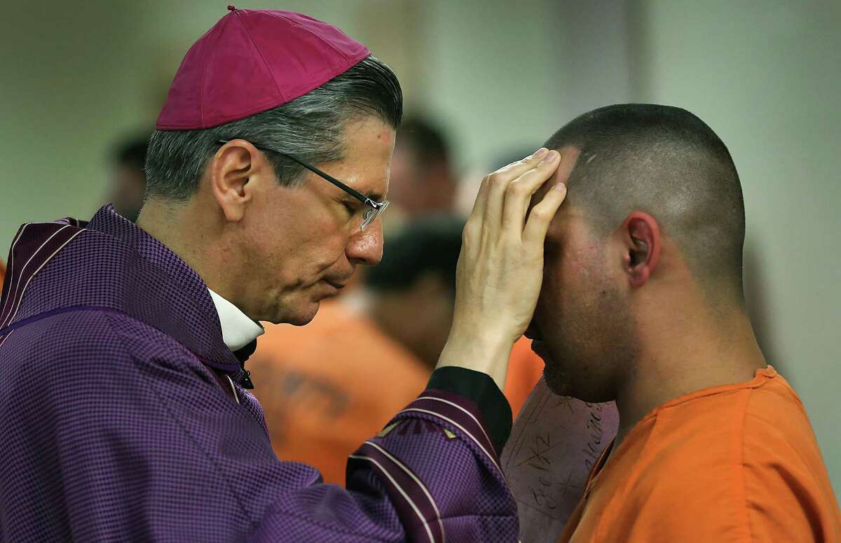 Archbishop Gustavo Garcia-Siller, a regular visitor to the Bexar County jail, celebrated Mass for 47 incarcerated mothers on Thursday. In this file photo, he blesses an inmate following a Christmas Mass in 2014.