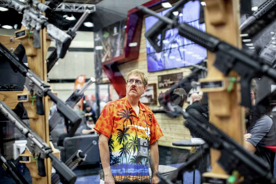 A man looks over AR-15 style rifles in the exhibition area during the National Rifle Association annual convention in Dallas. About 75,000 NRA members gathered for their annual convention. They attended gun shows, concerts, workshops and political speeches, including ones by President Donald Trump and Vice President Mike Pence. Photo: ASHLEY GILBERTSON, STR / NYT / NYTNS