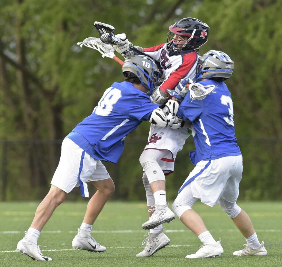 New Fairfield's Matt Constantides (23) is wedged between Glastonbury's Samuel Segal (18) and Hunter Wallace (3) in the boys lacrosse game between Glastonbury and New Fairfield high school, Thursday night, May 10, 2018, at New Fairfield High School, New Fairfield, Conn. Photo: H John Voorhees III / Hearst Connecticut Media / The News-Times