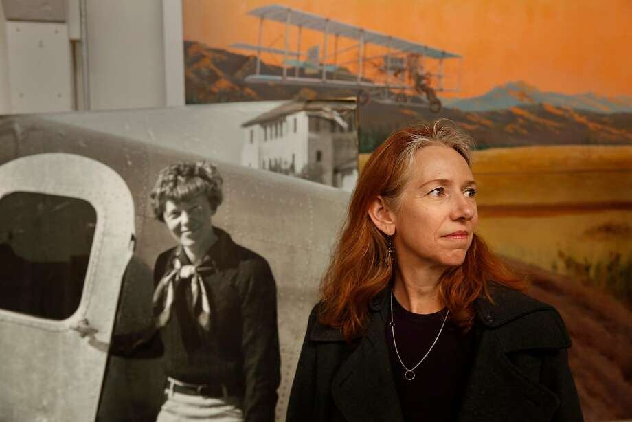 Wendy O'Malley, a corporate pilot who's been flying for more than 20 years, stands before a portrait of Amelia Earhart. Photo: Michael Macor / The Chronicle
