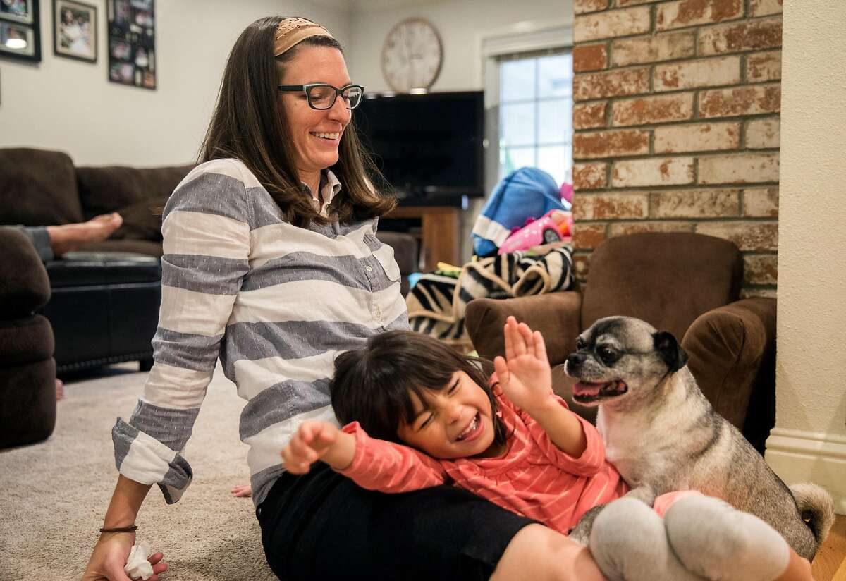 Jessica Quiambo, a behavioral analyst, laughs with her daughter, Grace, 3, and their dog Bandit at her home in Tracy, Calif. before heading to work Saturday, May 5, 2018.