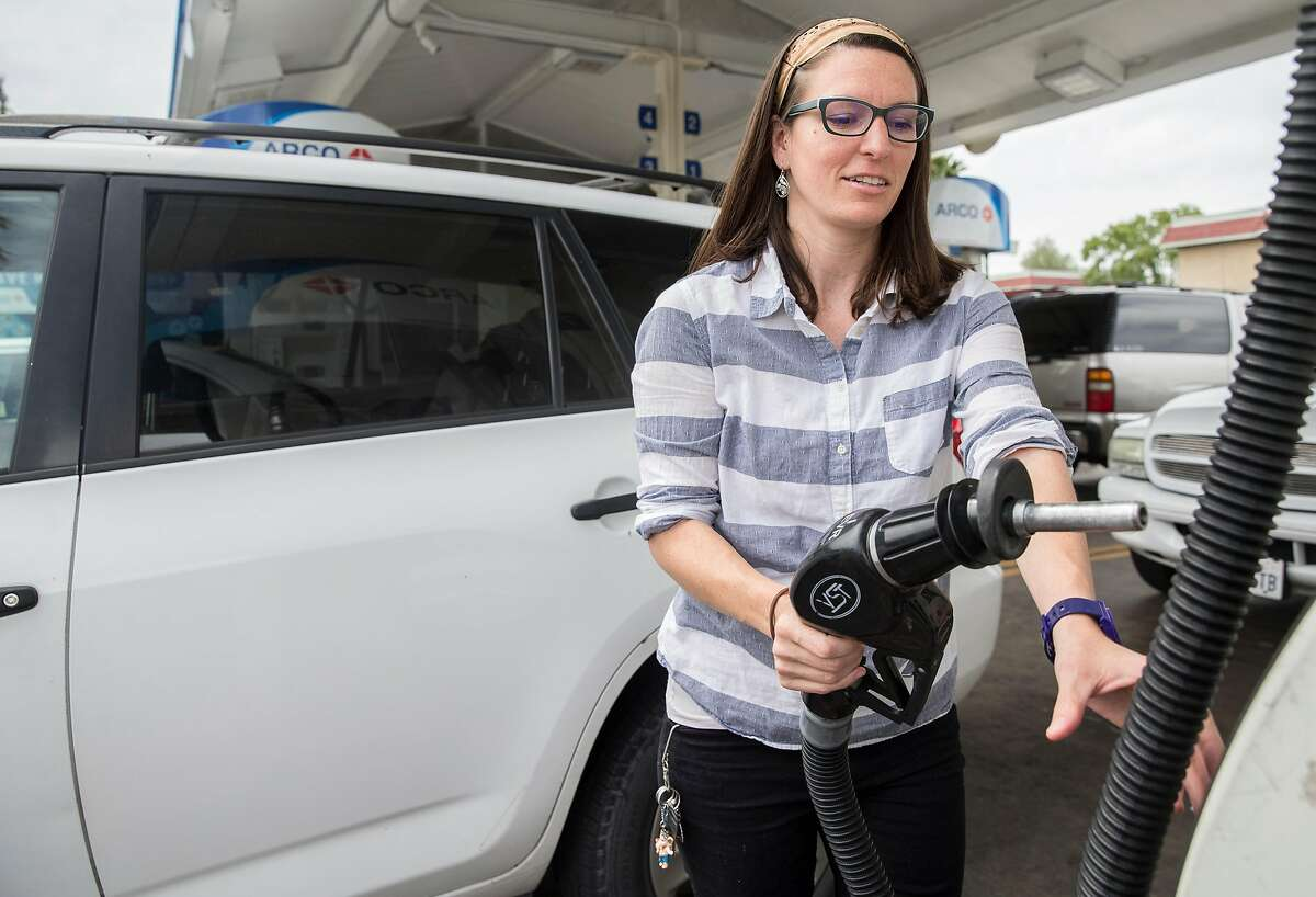 Jessica Quiambo, a behavioral analyst, pumps gas in Tracy, Calif. Saturday, May 5, 2018 before making the one hour drive to work in Fremont, Calif.