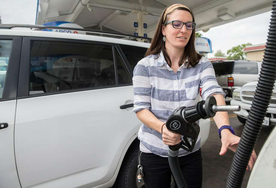 Jessica Quiambao, a behavioral support analyst, fills the tank in Tracy before making the hour-long drive to see a client in Fremont. Photo: Jessica Christian / The Chronicle