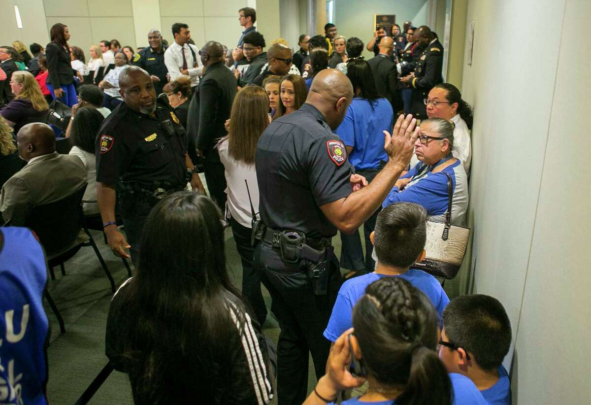 Police ask people to clear the back of the room and watch from an overflow room before the Houston Independent School District board meeting, Thursday, May 10, 2018, in Houston. Officials did not want people standing in the back of the room, keeping the area clear except for members of law enforcement.