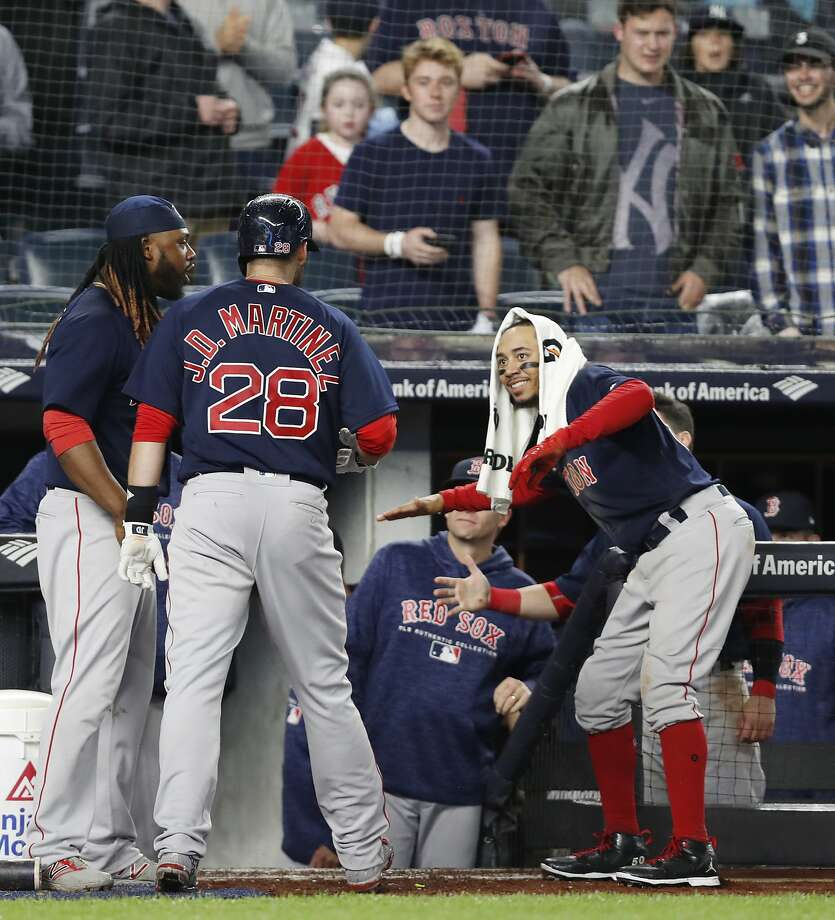 Mookie Betts (right) and Hanley Ramirez welcome J.D. Martinez back to the dugout after his homer. Photo: Kathy Willens / Associated Press