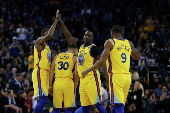 OAKLAND, CA - FEBRUARY 24: Kevin Durant #35, Stephen Curry #30, Draymond Green #23 and Andre Iguodala #9 of the Golden State Warriors celebrate during the game against the Oklahoma City Thunder at ORACLE Arena on February 24, 2018 in Oakland, California. NOTE TO USER: User expressly acknowledges and agrees that, by downloading and or using this photograph, User is consenting to the terms and conditions of the Getty Images License Agreement. (Photo by Lachlan Cunningham/Getty Images)