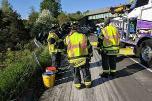Crews with the Danbury Fire Department work on an overturned truck on Intestate 84 Friday.