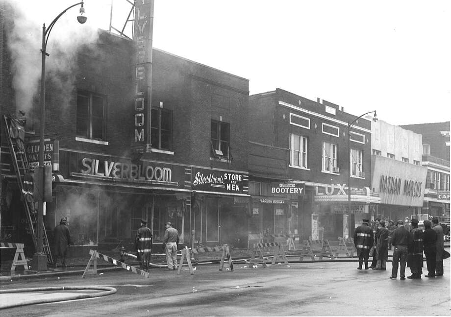The above photograph was taken February 14, 1956, after the fire in the Overbeck buildings. It is one of the few photographs where all of the Overbeck family's improvements can be seen. On the far left is Overbeck's Wallpaper and Paint, then the original Silverbloom store, the addition which has the sign for Silverbloom's Mens, and the Fashion Bootery, now home to Bin 51 Wine and Spirits.