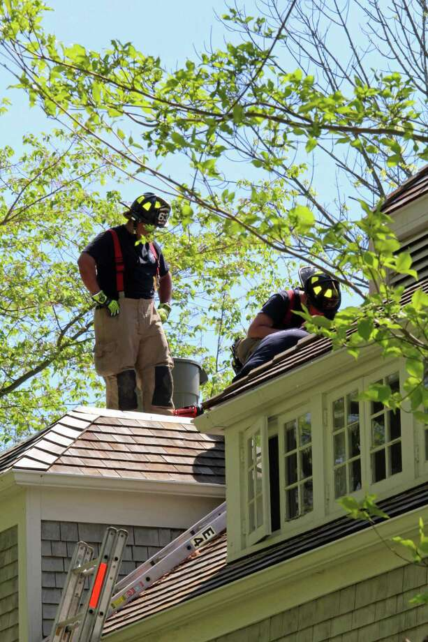 Firefighters on the roof of a home on Cannon Road in Wilton where a fire started Friday morning as electricians were working. Photo: Thane Grauel / Hearst Connecticut Media / Connecticut Post