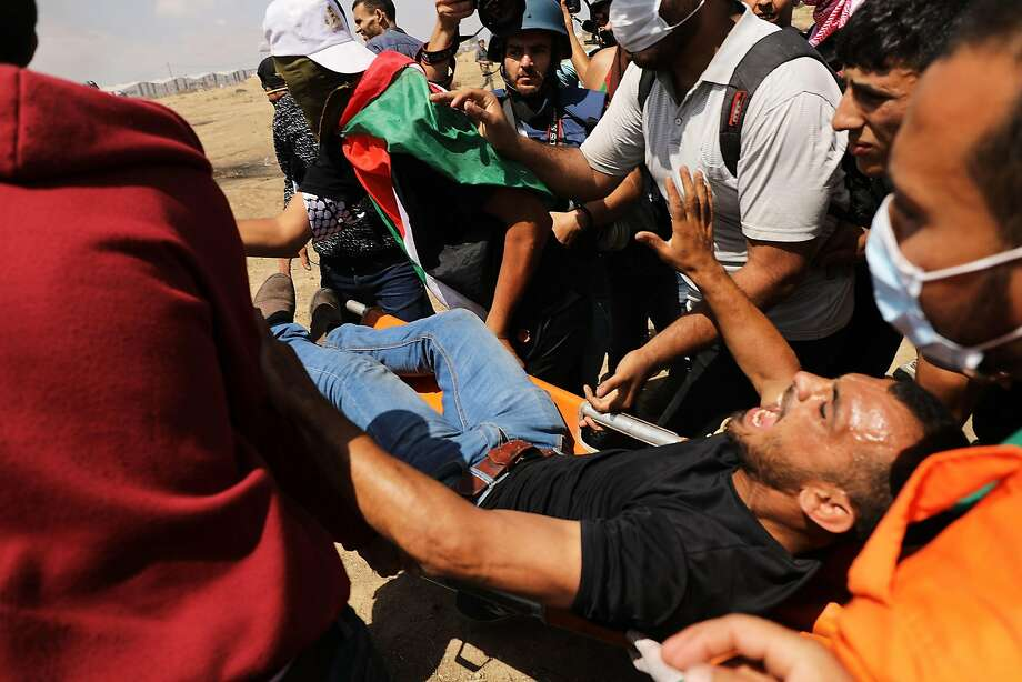 A Palestinian man is rushed to an ambulance at the border fence. Gaza's Hamas rulers say the protests will continue until the Israeli blockade is lifted. Photo: Spencer Platt / Getty Images