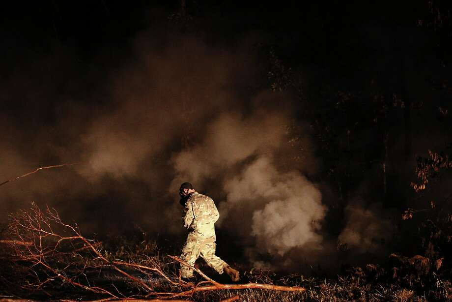 Sgt. Carl Satterwaite of the National Guard tests air quality near cracks emitting volcanic gases from a lava flow in the Leilani Estates subdivision near the town of Pahoa on Thursday. Photo: Jae C. Hong / Associated Press