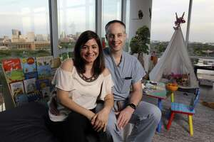 Rivka Colen and Pascal Zinn in the toy strewn living room of their 11th floor apartment overlooking Rice University and the medical center. Pascal and Rivka rescued some 16 neighbors from their flooded homes on Braesvalley, where they lived when Hurricane Harvey hit last year.