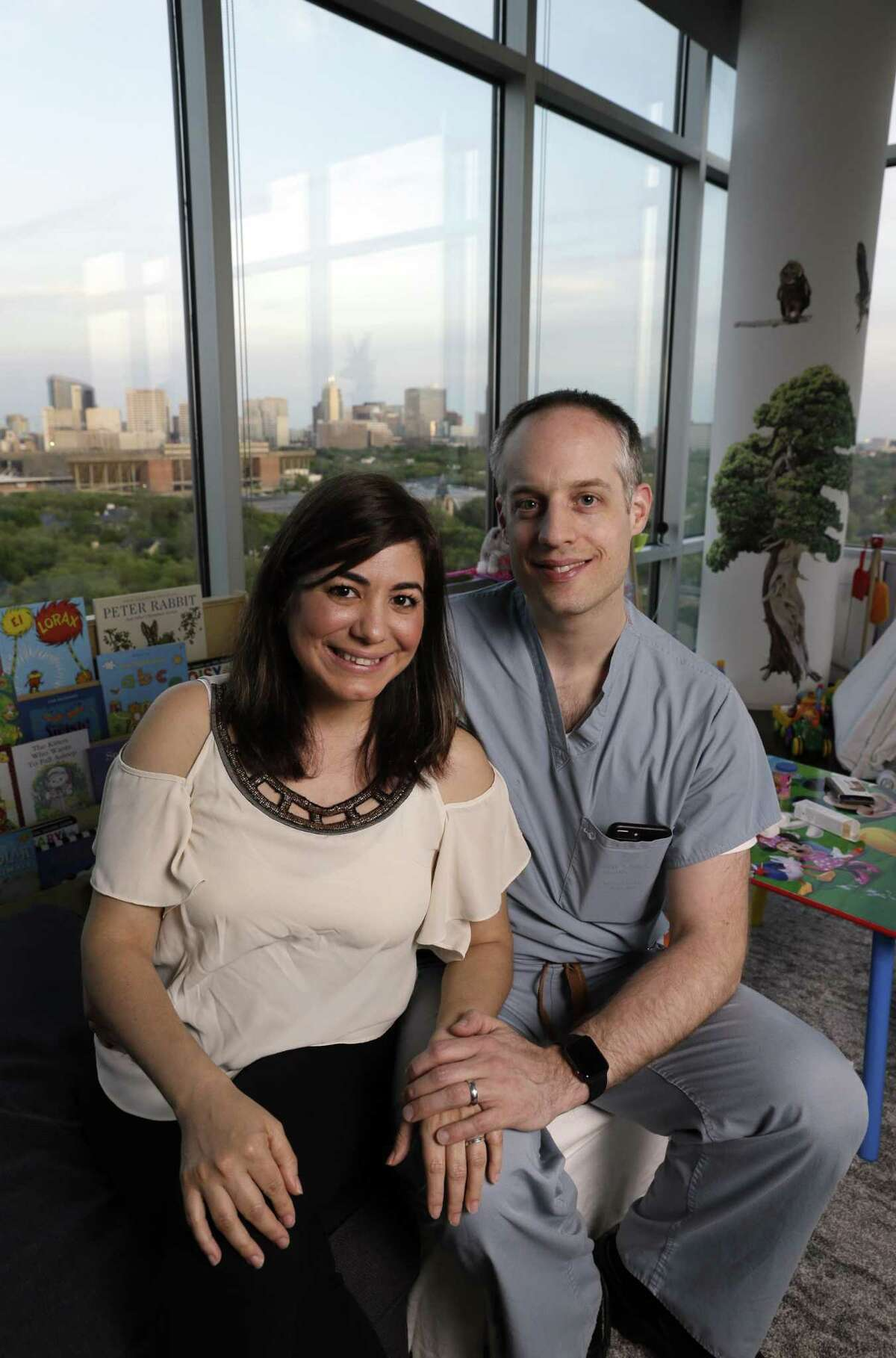 Rivka Colen and Pascal Zinn in the toy strewn living room of their 11th floor apartment overlooking Rice University and the medical center. Pascal and Rivka rescued some 16 neighbors from their flooded homes in Meyerland, where they lived when hurricane Harvey hit last year.
