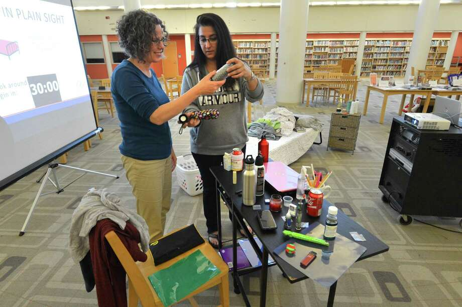"Margaret Watt and Deb Ryan find some of the items like a water bottle with a false bottom that are decoys planted in a mock bedroom with clues of high-risk behavior Thursday May 10, 2018 at Brien McMahon High School in Norwalk Conn. The workshop, ""Hidden in Plain Sight,"" is hosted by Norwalk Public Schools, the Connecticut Association of Prevention Professionals, Positive Directions and the Human Services Council in light of National Prevention Week, which starts May 14. Photo: Alex Von Kleydorff / Hearst Connecticut Media / Norwalk Hour"