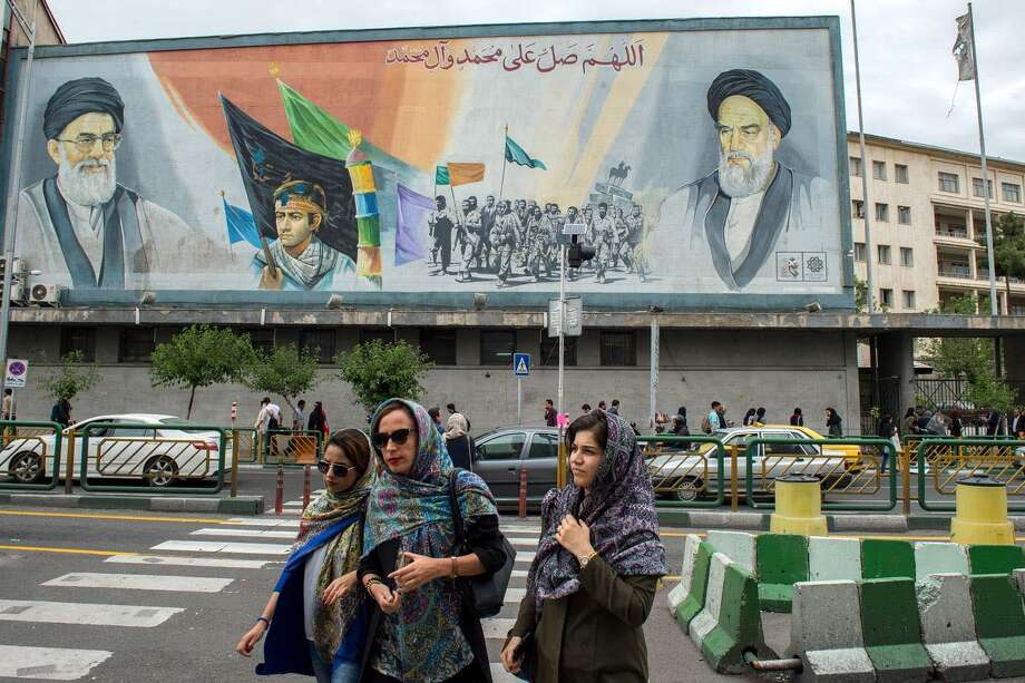 Women cross a street near a giant political mural depicting Ayatollah Ali Khamenei, Iran's supreme leader, left, and Ayatollah Ruhollah Khomeini, founder of the Islamic Republic of Iran, in Tehran, in May. Photo: Bloomberg Photo By Ali Mohammadi. / Bloomberg