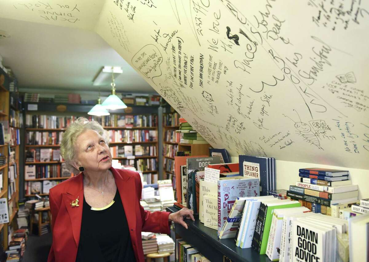 Diane Garrett looks at the wall of compliments written by her customers over the years at Diane's Books in Greenwich.
