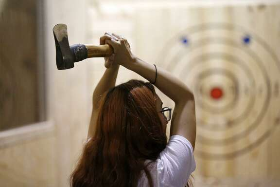 Lucy Barbosa learns how to throw an axe, Thursday May 10, 2018, at San Antonio Axe Throwing Class Axe.