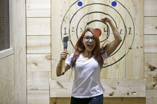 Lucy Barbosa celebrates after sticking an axe, Thursday May 10, 2018, at San Antonio Axe Throwing Class Axe.