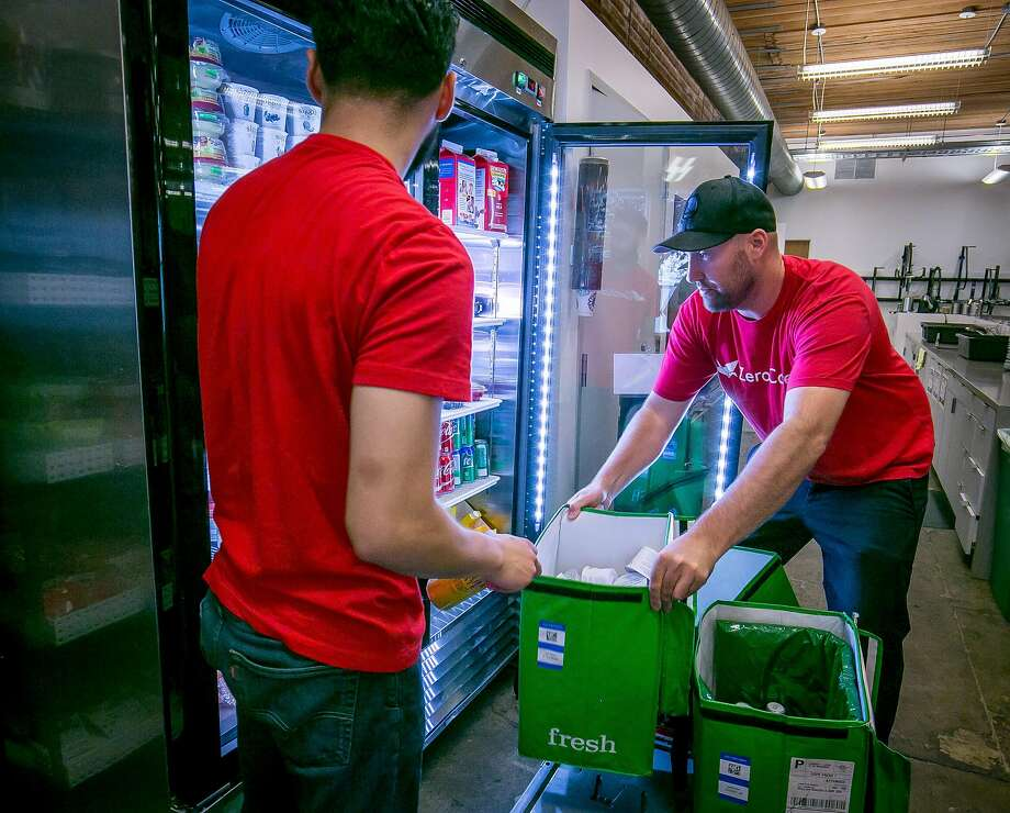Mike Joritz (right) and Jefry Romero from ZeroCater stock the officer of MemSQL in San Francisco with snacks and drinks last year. Photo: John Storey / Special To The Chronicle 2017