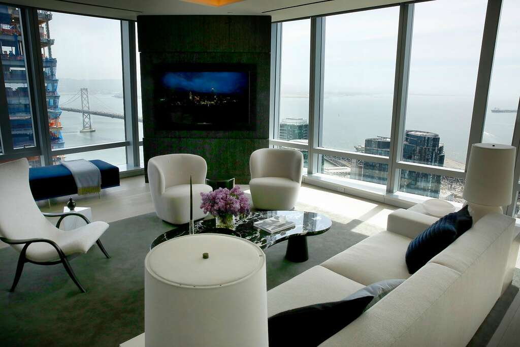 The Sky Lounge, top, looks out over the Bay Bridge from the 39th floor of 181 Fremont St. Above, the living room in the model residence at the skyscraper. Photo: Michael Macor / The Chronicle