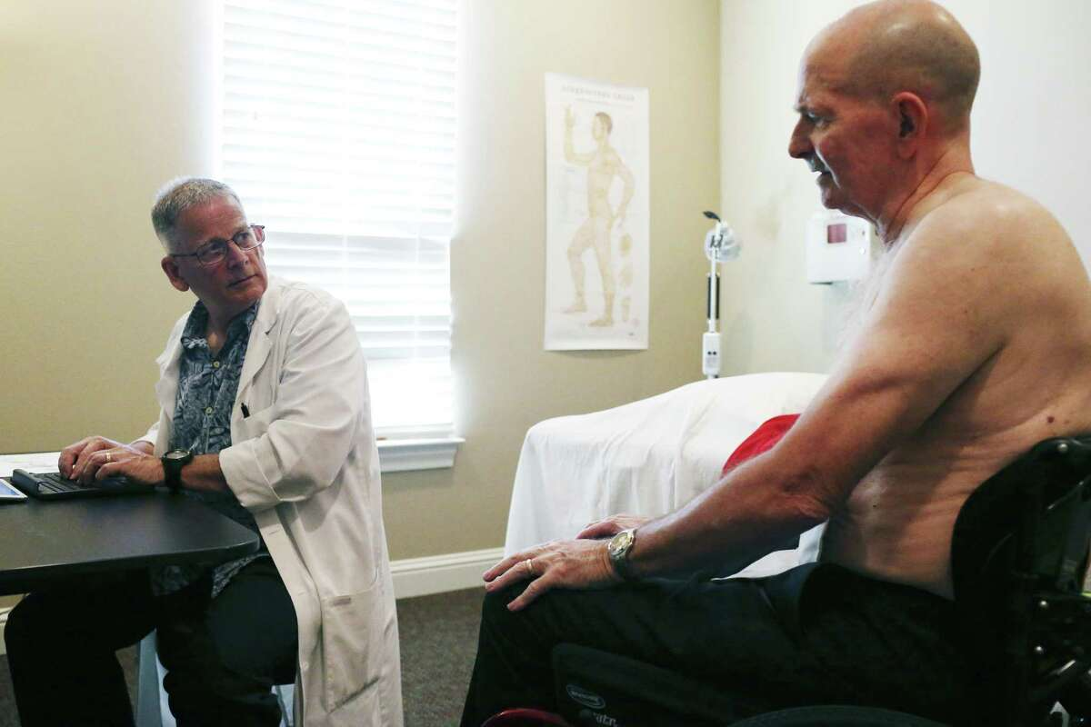 Acupuncturist Michael Callaghan, left, takes information from David K. Winnett, Jr., of New Braunfels, during a visit for pain relief treatments, Monday, May 7, 2018. Winnett, 63, is a former Marine captain with 100% disability due to his gulf war illness created by exposure to nerve gases and other toxic chemicals. He is a paraplegic after surgery related to a service-related back ailment.