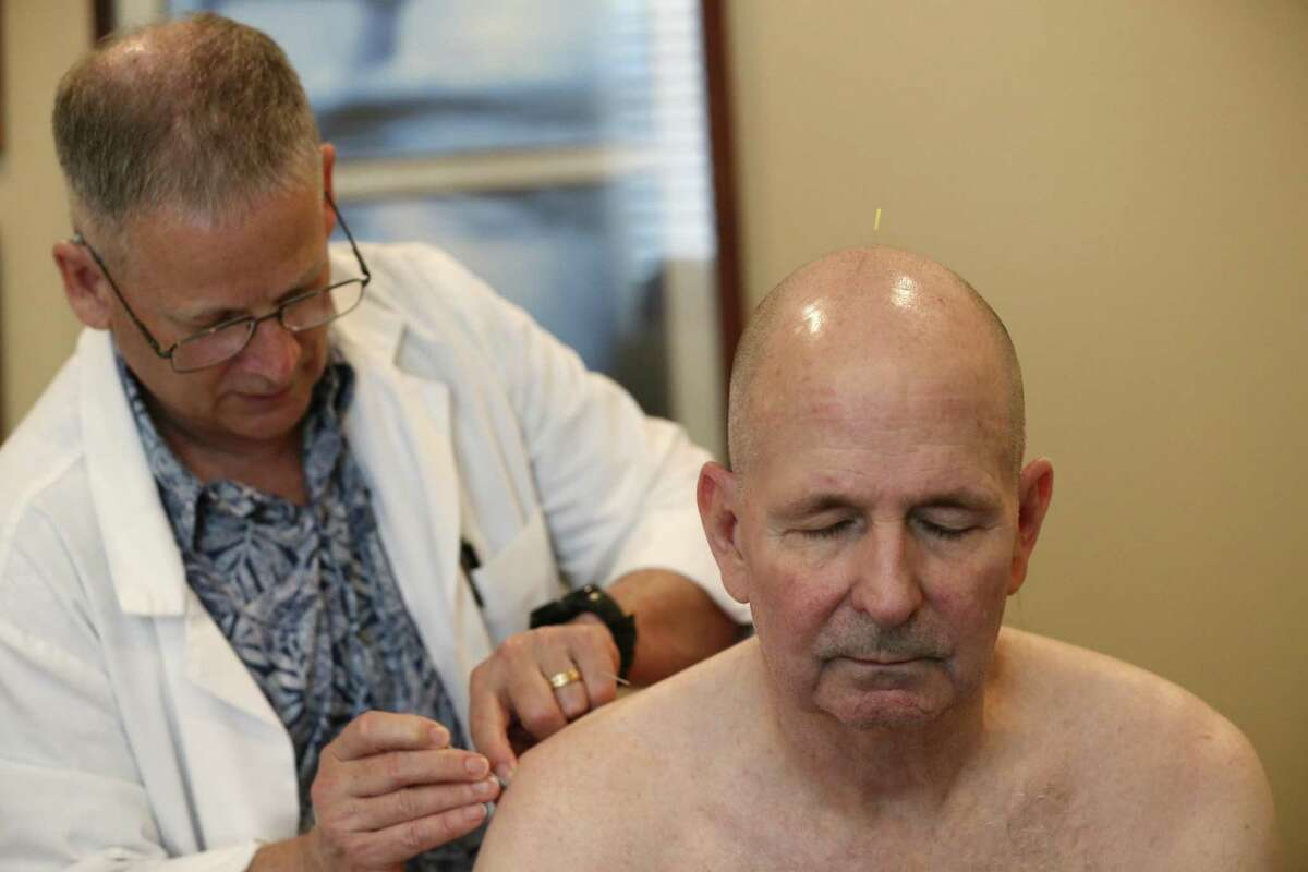 Acupuncturist Michael Callaghan, left, works on David K. Winnett, Jr., of New Braunfels, during a visit for pain relief treatments, Monday, May 7, 2018. Winnett, 63, is a former Marine captain with 100% disability due to his gulf war illness created by exposure to nerve gases and other toxic chemicals. He is a paraplegic after surgery related to a service-related back ailment.