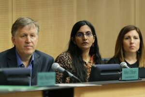 Seattle City Council members Kshama Sawant, center, Mike O'Brien, left, and Teresa Mosqueda, right, listen to public comments on a controversial proposal to tax large businesses such as Amazon.com to fund efforts to combat homelessness, Wednesday, May 9, 2018, during a Seattle City Council committee meeting at City Hall in Seattle. (AP Photo/Ted S. Warren)