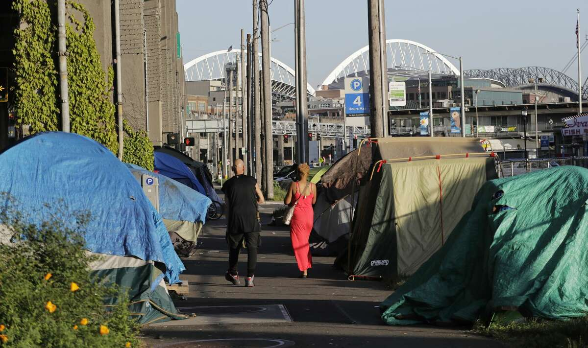 In this Monday, May 7, 2018 photo, with CenturyLink and Safeco Fields in the background, two people walk past a half-dozen tents set up along a sidewalk at the Seattle waterfront. Seattle's latest tax proposal to combat homelessness takes aim at large businesses such as Amazon that have helped drive the city's economic boom. But businesses and others say the so-called head tax is misguided and potentially harmful and they question whether the city is effectively using the tens of millions of dollars it already spends on homelessness each year. (AP Photo/Ted S. Warren)