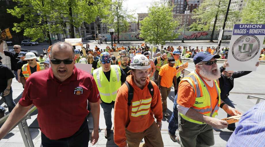 Ironworkers and other union members chant and hold signs as they march up the steps of Seattle City Hall, Wednesday, May 9, 2018, in Seattle, during a City Council committee meeting that included consideration of a controversial proposal to tax businesses such as Amazon to fund efforts to combat homelessness. The workers who were marching oppose the proposed tax. (AP Photo/Ted S. Warren) Photo: Ted S. Warren/AP