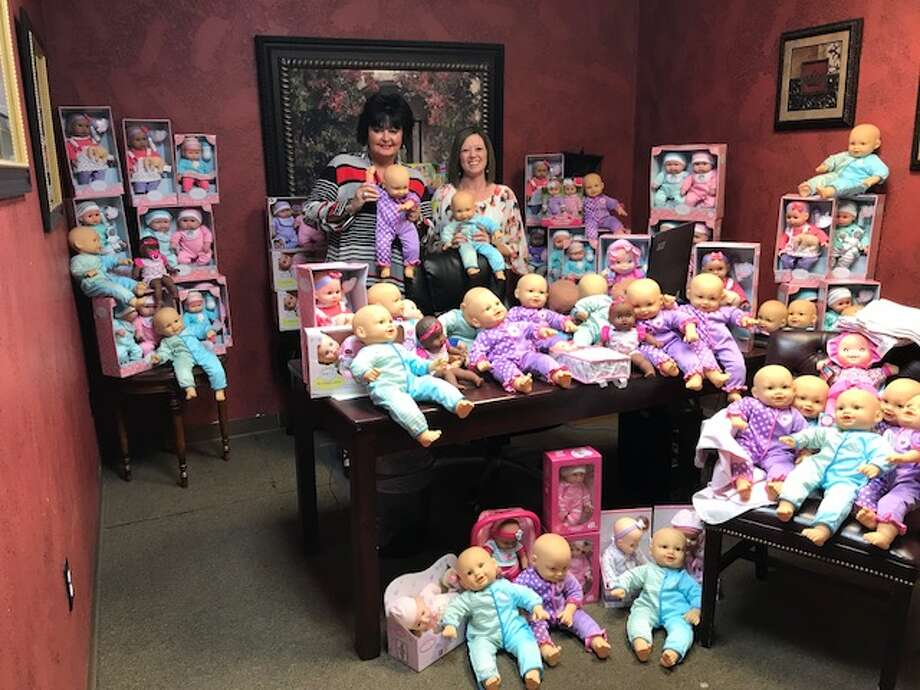 Mary Wright-McCourt, left, and Julie Gray show off the dolls they collected for their project, Angie's Babies. The dolls will be distributed today to women in nursing homes who are Alzheimer's patients. Photo: Courtesy Photo