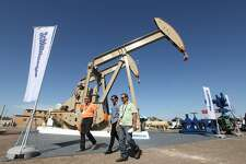 Oil show attendees walk past the Schlumberger booth at the Permian Basin International Oil Show at Ector County Coliseum on Tuesday, Oct. 18, in Odessa, Texas. (Jacob Ford/Odessa American via AP)