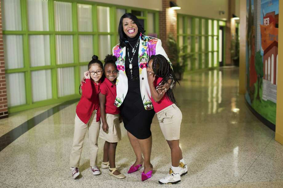 Peck Elementary principal Carlotta Brown gives daily hugs to students, like Valerie Lopez, Dea'Myah Malveaux and Peyton Woods.  Photo: Marie D. De Jesus,  Houston Chronicle / Houston Chronicle / © 2018 Houston Chronicle