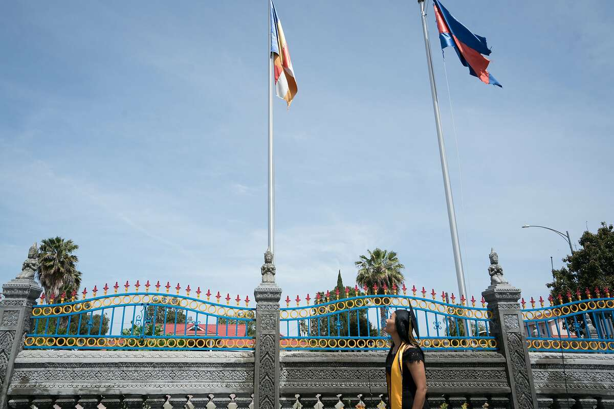 Chansitha Ouk looks toward the Cambodian, Buddhist and Californian flags in front of the Cambodian Buddhist Society temple in San Jose, Calif. on Thursday, May 10, 2018.