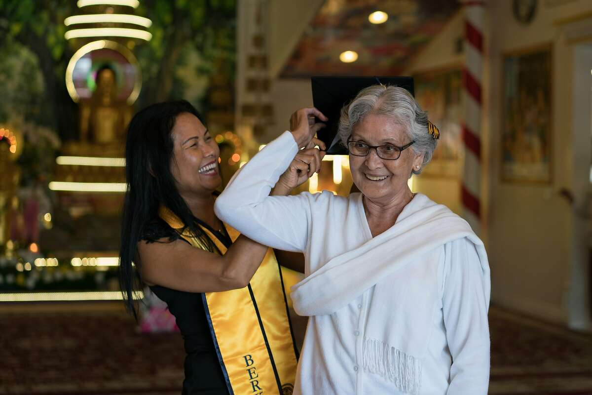 Ouk places her graduation cap on her mother's head inside the Buddhist temple in San Jose.
