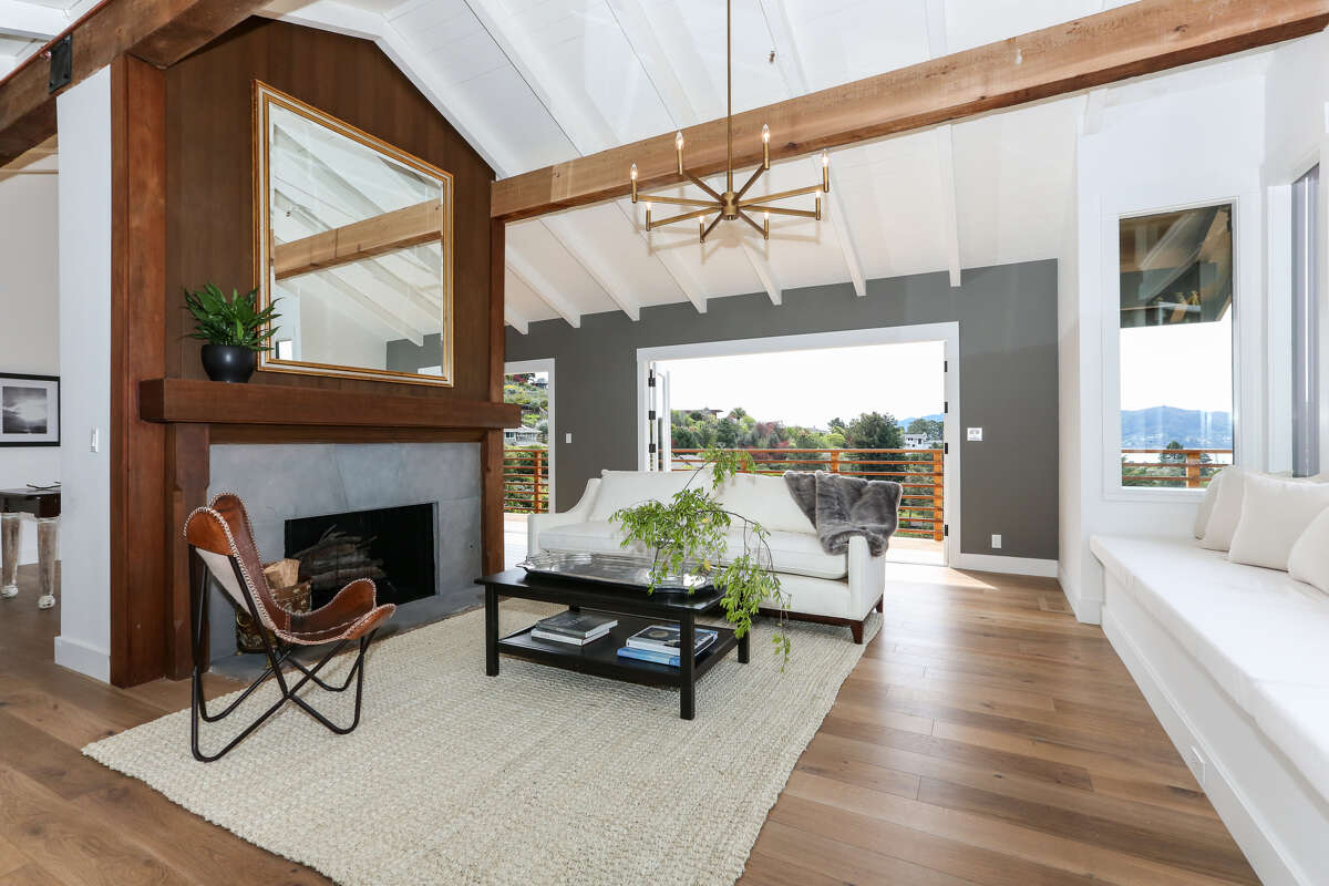 The living room features hardwood flooring, a vaulted, beamed ceiling and wood-burning fireplace.