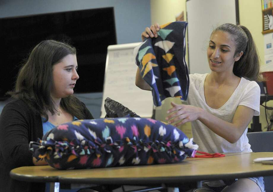 Amanda Merritt, 13, left, and Angela Carrozza, 14, display their tie pillows that they made for the homeless, Friday, May 11, 2018. A New Fairfield Middle School program called Project Citizenship, which encourages students to come up with action plans for a problem they identify in the community or the world, is coming up on its five year anniversary. Photo: Carol Kaliff / Hearst Connecticut Media / The News-Times