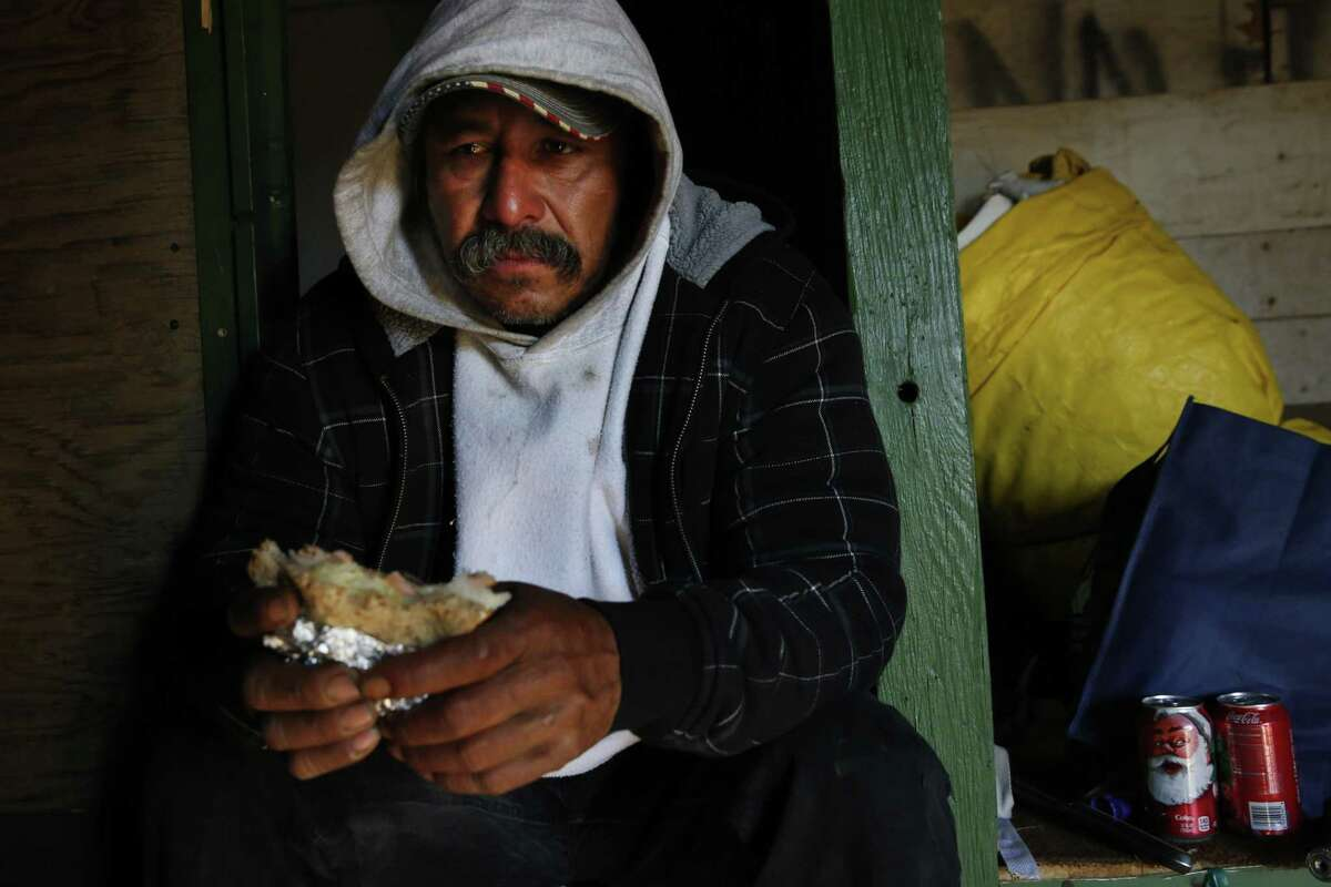 """Mart?'n Hernandez Mena, 50, becomes tearful as he eats his donated lunch inside of his home as he waits for the police to show up to evict him and the other residents from the shantytown which is situated in a dried up canal on Westlands Water District land Nov. 20, 2015 outside of Mendota, Calif. Mena has lived for a year and a half in the canal bed after he could no longer afford rent in town. Mena has lived in the U.S. for 12 years and has four grown children in Mexico, where he is from. He used to have steady farm work, starting with water melons, cantaloupes, grapes, tomatoes and pomegranate. The last few years he worked in pistachios and almonds and it was five years ago that he last had steady work as an employee. Since then, he says, it has been harder to find work. Mena mostly survives by doing work for others who live in the shantytown, such as building and fixing things for them. Sometimes he finds odd jobs in Mendota working for people in town. """"I keep thinking and hoping of finding ways to get out of this canal. Once I?•m free from that, I can focus on other things.?"""" Mena said in Spanish. ?'All your energy goes to just getting by here."""" Those who live in the encampment and others from Mendota say that there have been a small number of structures in the canal bed for years. But as California entered into the third and fourth years of one of the worst droughts in its modern history, the shantytown bloomed to nearly 30 structures. Mendota has a population of about 11,500 people with more than 40 percent of the population living below the poverty line. Steady work has become more and more difficult to find for community members who depend heavily on the agriculture industry. After months of litigation, Westlands Water District evicted the shantytown residents in November."""