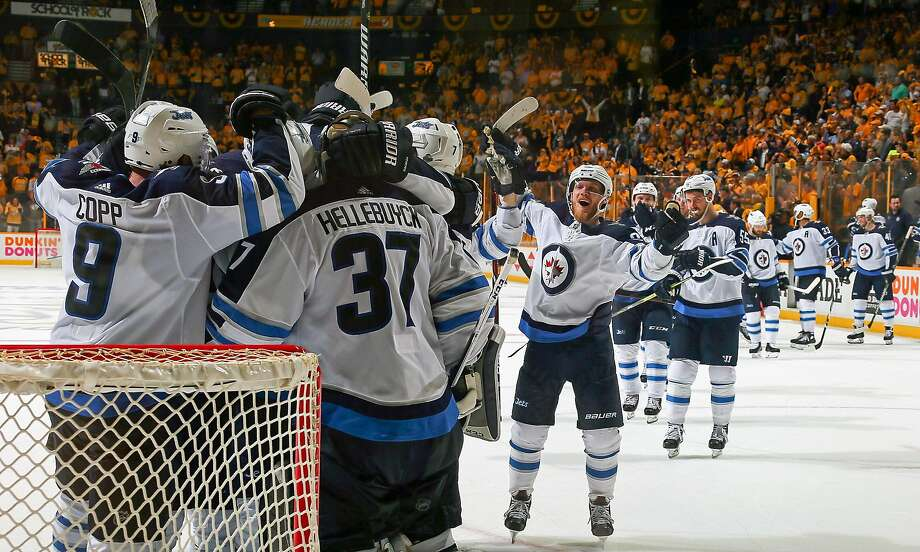 Andrew Copp #9 and Connor Hellebuyck #37 of the Winnipeg Jets celebrate with their teammates after a 5-1 Jets Victory in Game Seven of the Western Conference Second Round during the 2018 NHL Stanley Cup Playoffs at Bridgestone Arena on May 10, 2018 in Nashville, Tennessee. (Photo by Frederick Breedon/Getty Images) Photo: Frederick Breedon / Getty Images